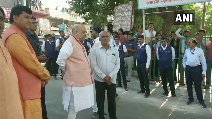 गुजरात: अहमदाबाद के रानिप में निशान हायर सेकेंडरी स्कूल में पोलिंग बूथ के पास, भाजपा अध्यक्ष अमित शाह इंतज़ार कर रहे । पीएम नरेंद्र मोदी शीघ्र ही मतदान केंद्र पर अपना वोट डालेंगे।
